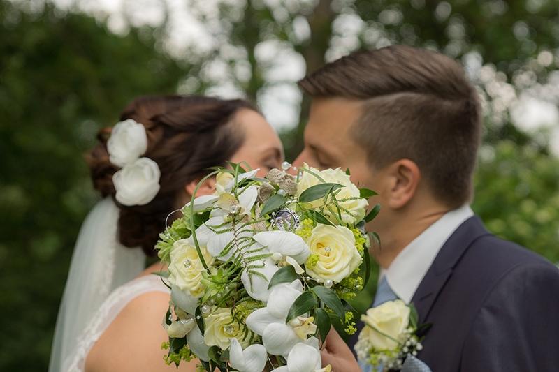 Kuss eines Brautpaares hinter dem Brautstrauß