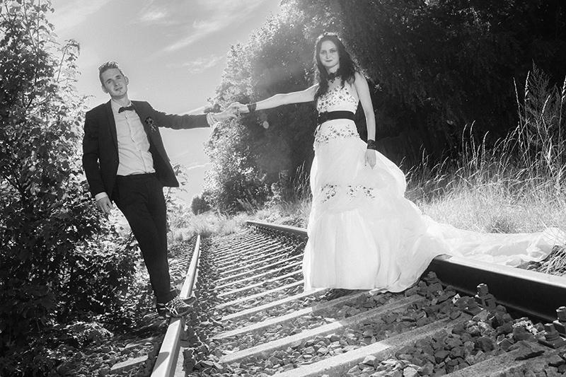 Scharz-Weiß-Aufnahme von einem Brautpaar auf einem Bahngleis
