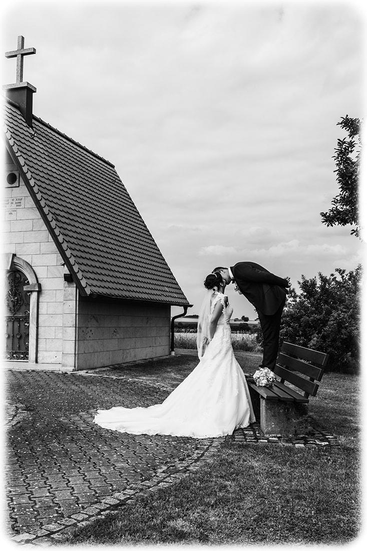 Brautpaar vor einer Kapelle auf einem Hügel